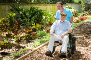 staff and senior male in wheelchair